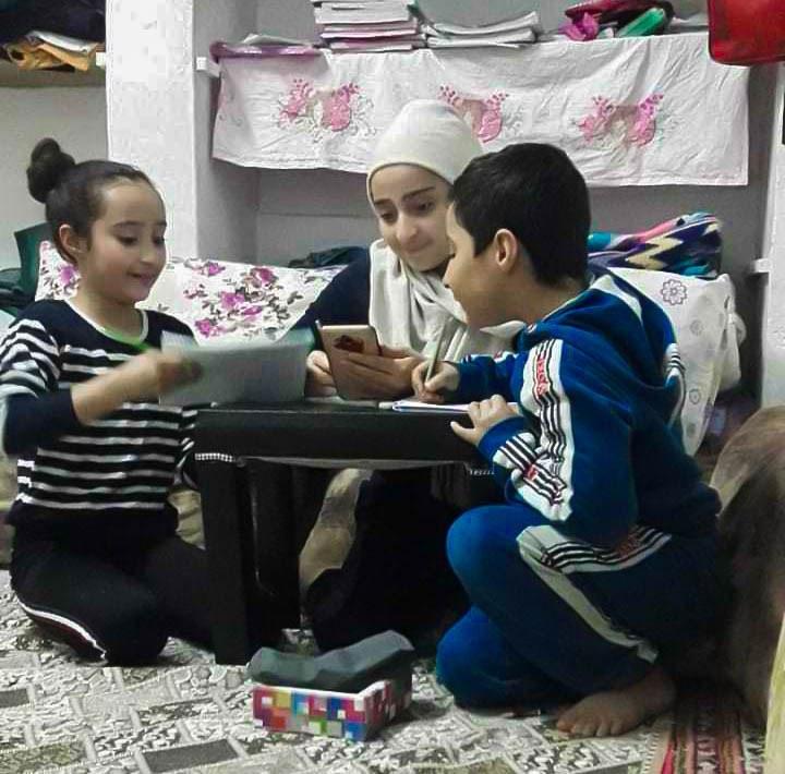 Three children learning through a smartphone